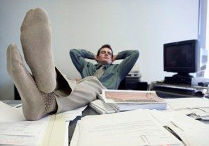 Businessman Relaxing at Desk with Feet Up