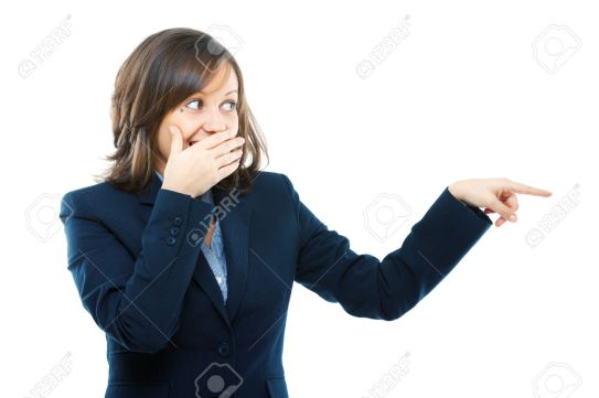 Businesswoman pointing and secretly laughing isolated on white background