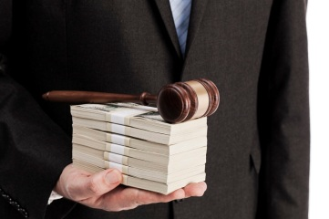 Man in suit holding stack of money and wooden gavel