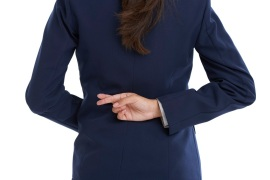 Rear view shot of a businesswoman with her fingers crossed behind her back in studio